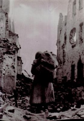 Kobieta z tobołkiem w ruinach. Ze zbiorów Stanisława Laguna