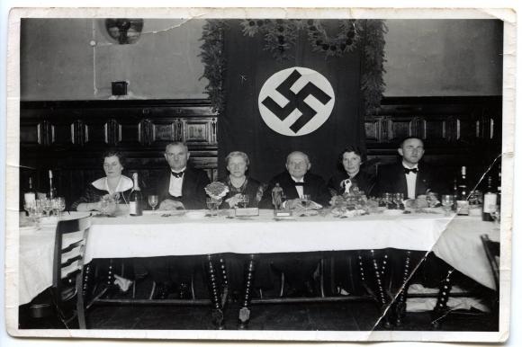 Teściowie Williego Beermanna w jednej ze szczecińskich restauracji podczas rocznicy ślubu na tle swastyki obecnej w tego typu miejscach. Muzeum Narodowe w Szczecinie