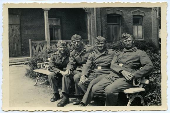 """Willy Beermann (drugi od prawej) w mundurze Luftwaffe. W oddali częściowo zamazany napis na ścianie """"Jude raus"""